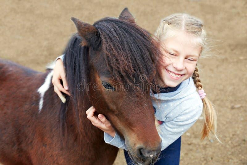 Ponny och liten flicka och hennes bästa vän royaltyfria bilder