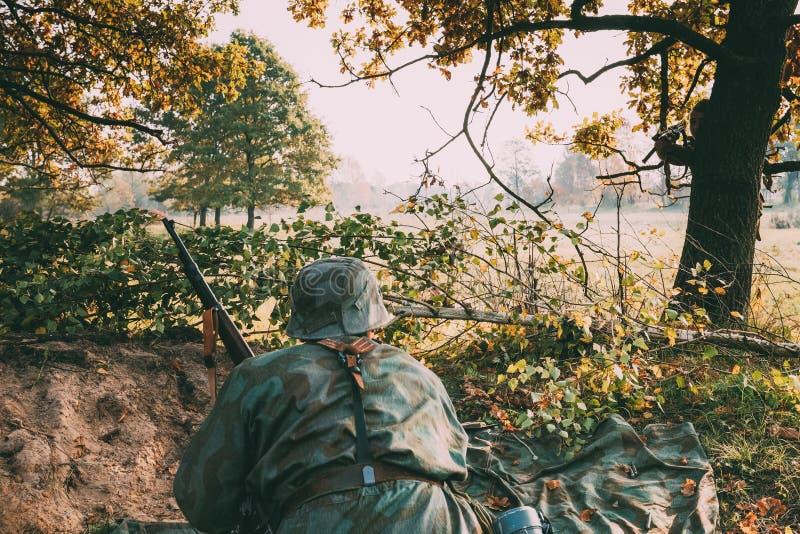 Ponowny Ubierający Jako niemiec Wehrmacht piechoty żołnierz W druga wojna światowa Chującym obsiadaniu Z Karabinową bronią Wewnąt zdjęcia stock