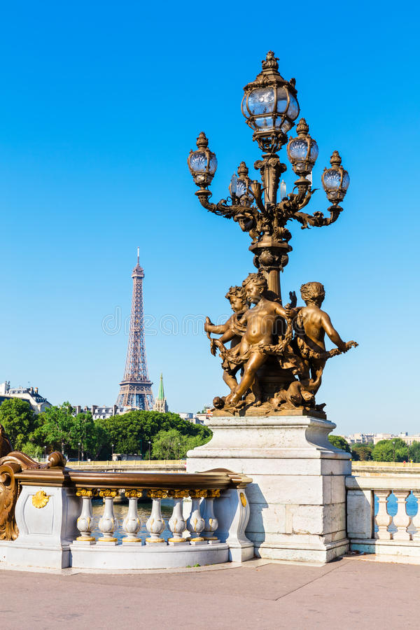 Pont Alexandre III Bridge (Lamp post details) and Eiffel Tower,. Ornate renaissance street lamp on the famous Pont Alexandre III bridge in central Paris with royalty free stock photography