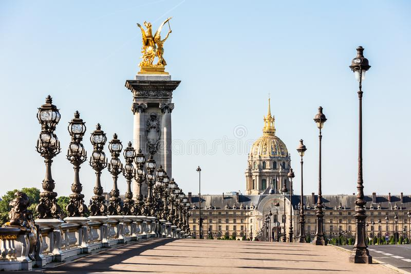 Pont Alexandre III bridge over the River Seine and the Hotel des Invalides in the background in the sunny summer morning. Bridge. Decorated with ornate Art stock photography