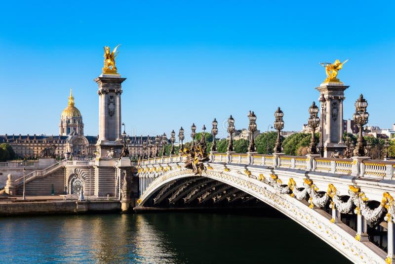 Pont Alexandre III bro med kupoldes Invalides, Paris arkivbilder