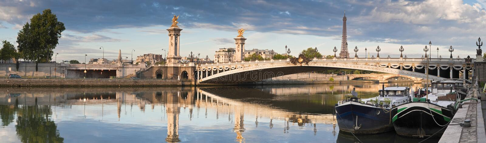 Pont Alexandre III and Eiffel Tower, Paris. Stunning Pont Alexandre III bridge (1896) spanning the river Seine. Decorated with ornate Art Nouveau lamps and stock photo