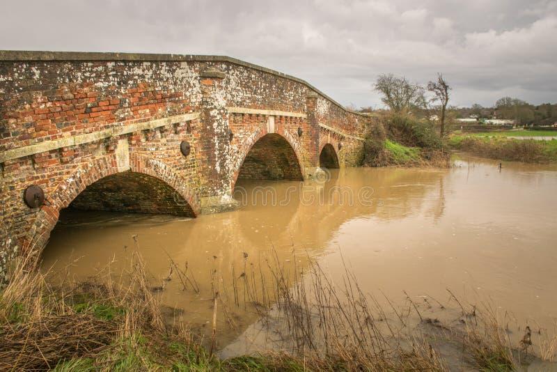 Pont assez vieux de brique au-dessus de rivière en crue photographie stock