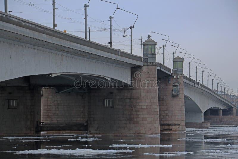 Pont au-dessus de la rivière avec les banquises de flottement photos stock