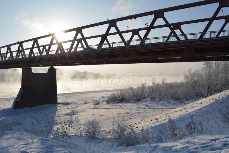 Pont au-dessus de la rivière, qui ne gèle pas, dans le jour d'hiver ensoleillé image libre de droits