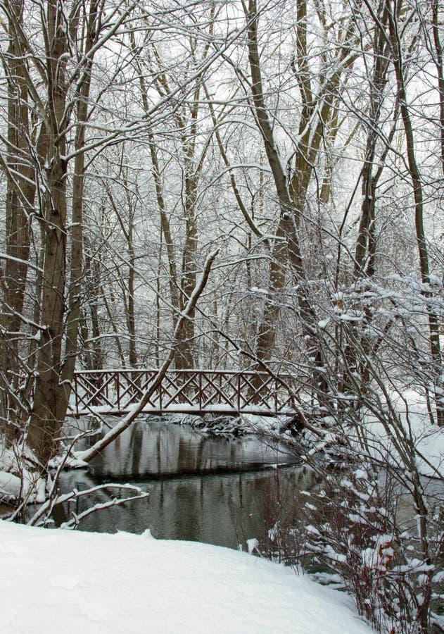 Pont couvert de neige au-dessus de crique images libres de droits