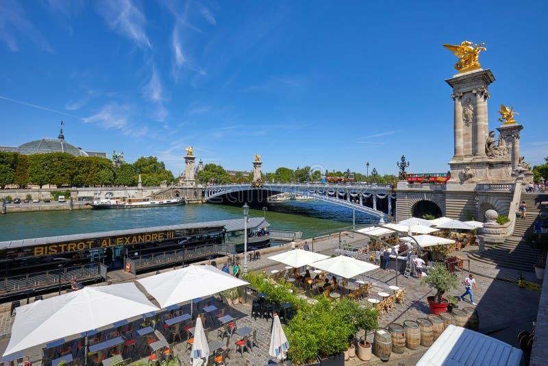 Pont d'Alexandre III avec des personnes et des touristes et caf? dans le secteur de docks dans un jour d'?t? ensoleill?, bleu image stock