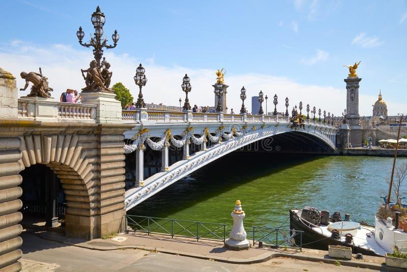 Pont d'Alexandre III avec les personnes et les touristes dans un jour ensoleillé, ciel bleu à Paris, France image stock