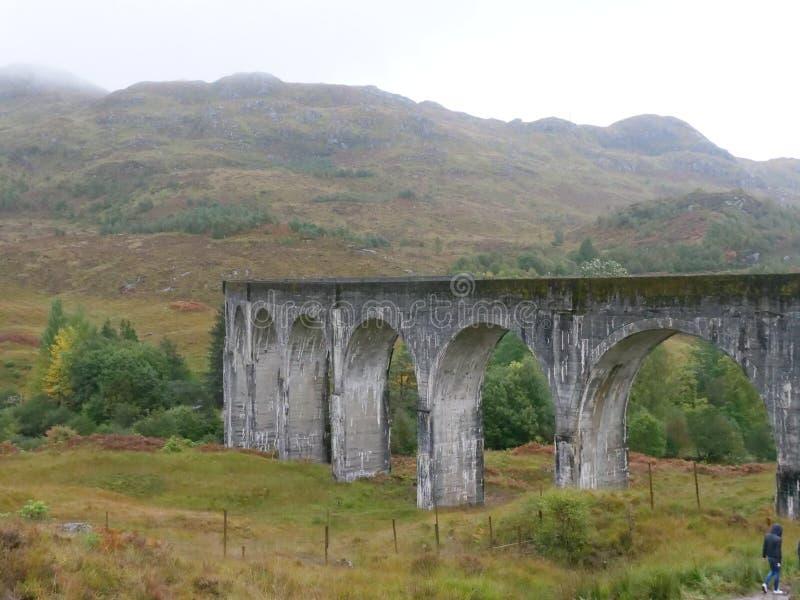 Pont de chemin de fer écossais Glenfinnan avec des montagnes photographie stock libre de droits