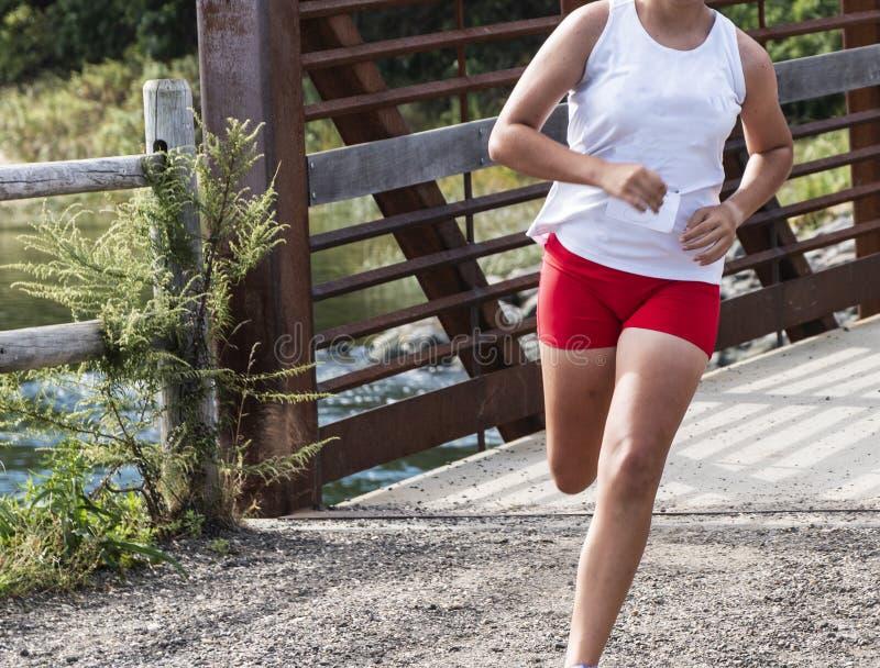 Pont de croisement femelle de coureur de lycée pendant la course photos stock