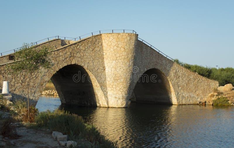 Pont de ` pont en pierre de ` de rire du petit, onduleux et raide vieux au-dessus de la manière méditerranéenne de l'eau de côte photos stock