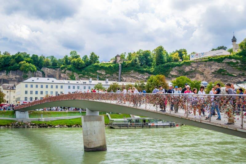 Pont de Markartsteg avec des cadenas et des touristes d'amour le croisant et prenant des photos à Salzbourg, Autriche Paysage urb image stock