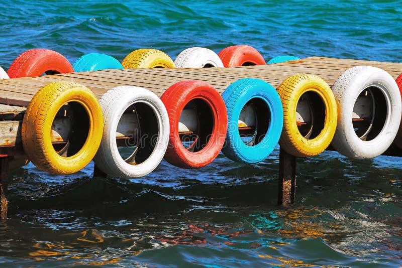 Pont de mer, pneus de couleur photos stock