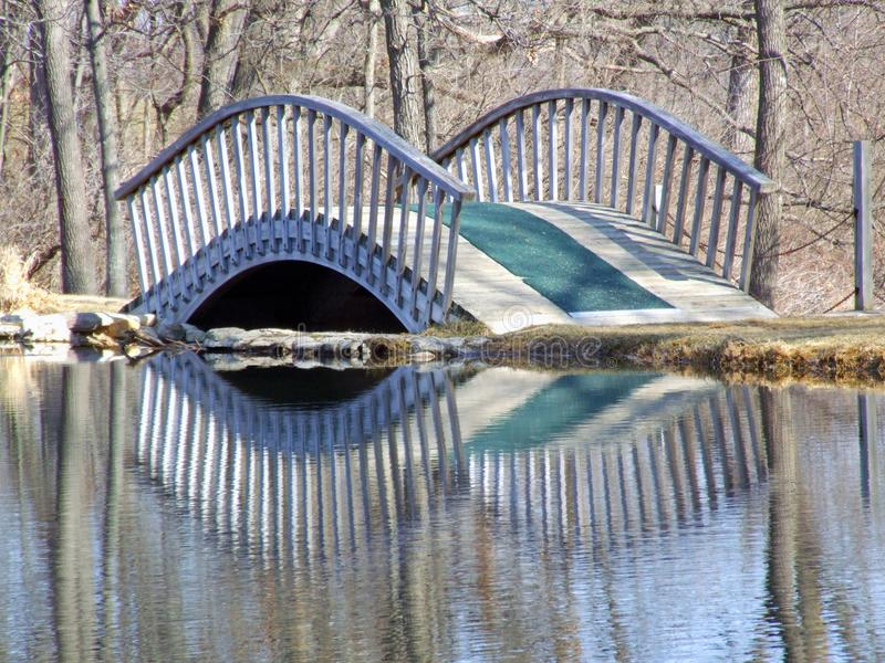Pont de pied reflété dans l'eau immobile photos libres de droits