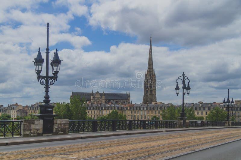 Pont de Pierre e basilica di St Michael con la sua torre sotto le nuvole, in Bordeaux, la Francia immagine stock libera da diritti