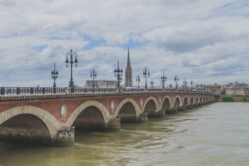 Pont de Pierre und Basilika von St Michael mit seinem Turm unter Wolken, im Bordeaux, Frankreich lizenzfreies stockfoto