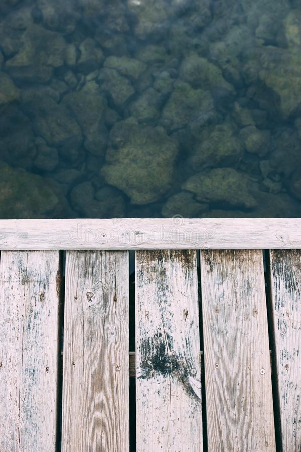Pont de plancher de conseil en bois et roches de l'eau et vertes claires photographie stock