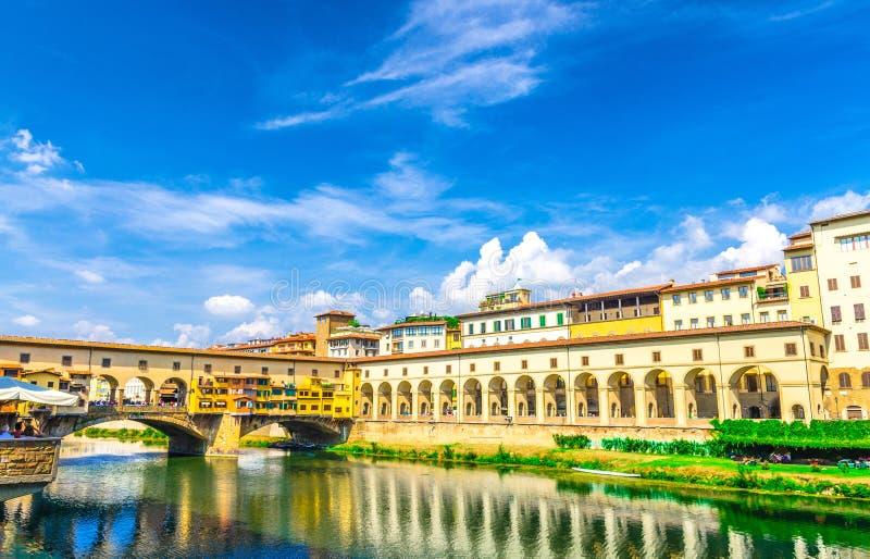 Pont de Ponte Vecchio avec les maisons colorées de bâtiments au-dessus de l'eau se reflétante bleue d'Arno River à Florence photographie stock
