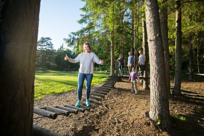 Pont de rondin heureux de croisement de jeune femme dans la forêt image libre de droits