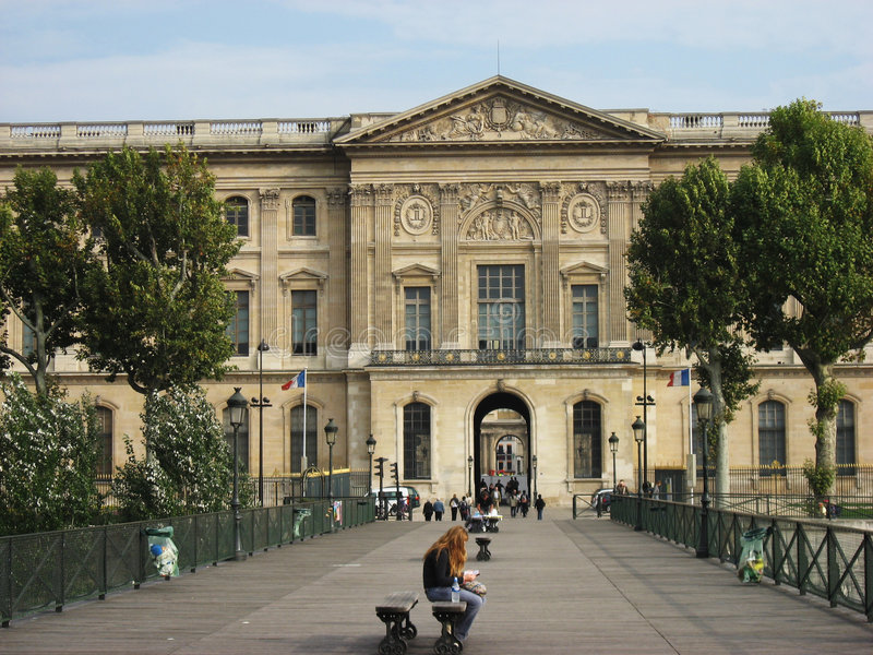 Pont des Arts Paris. The Pont des Arts bridge in Paris, France and the facade of the Louvre Museum historical building. A tourist is sitted in a bench in the royalty free stock photos