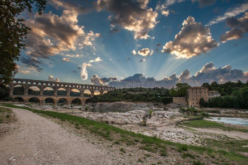 Pont du Gard en la puesta del sol con los rayos del sol imagen de archivo