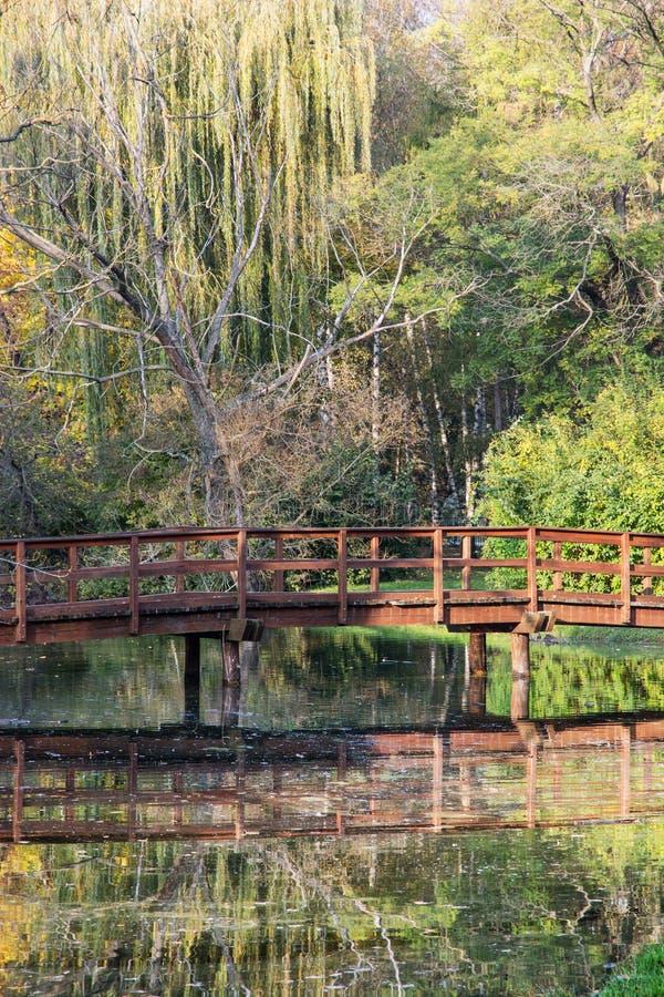 Pont en bois au-dessus d'étang reflété en parc d'automne photo stock