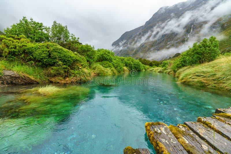 Pont en bois au-dessus de rivière dans les montagnes sous la pluie, Nouvelle Zélande 4 images stock