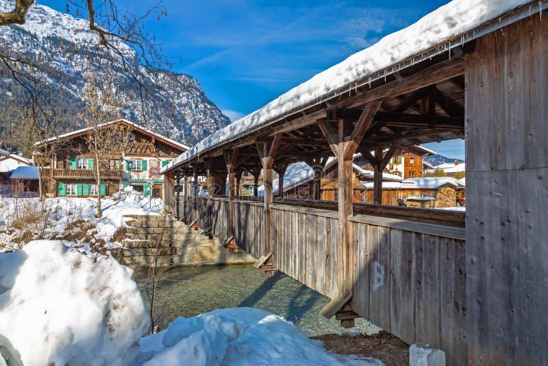 Pont en bois au-dessus de rivière de Loisach dans Garmisch Partenkirchen en hiver images stock