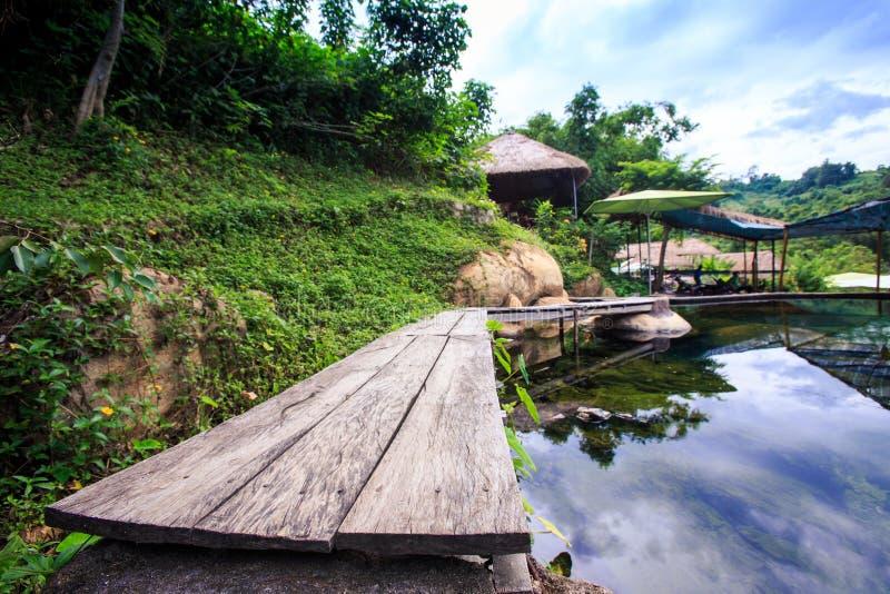 Pont en bois autour de réflexion de ciel d'étang en parc photo stock