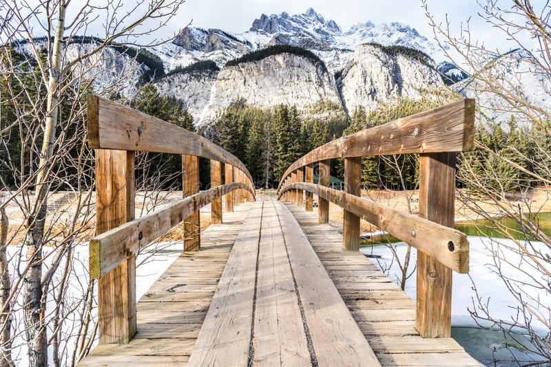 Pont en bois de pied menant au-dessus du courant glaciaire au wint de inspiration photo stock
