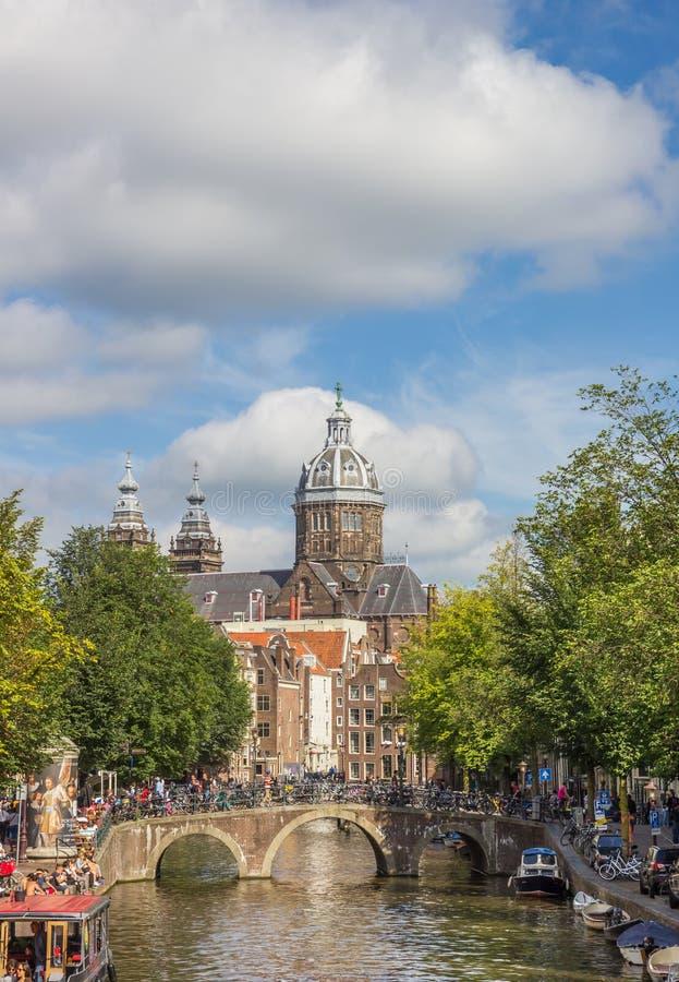 Pont en canal et l'église de St Nicolas à Amsterdam photographie stock