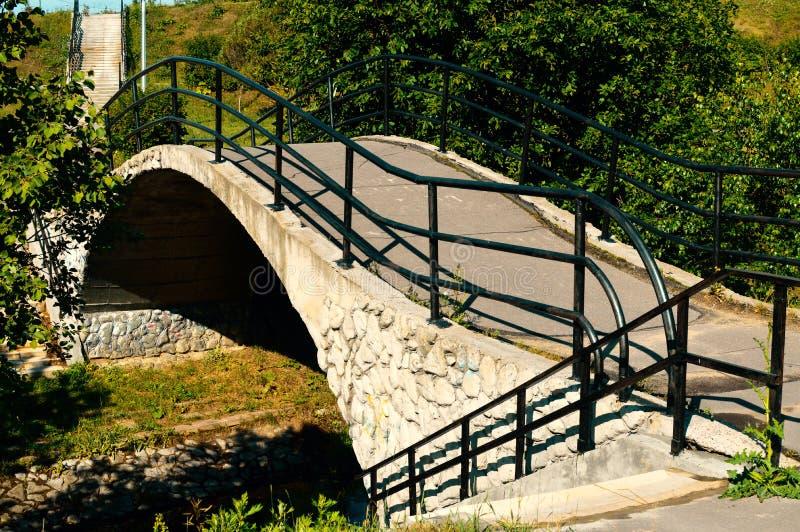 Pont en pierre au-dessus de peu de rivière en parc de ville photos libres de droits