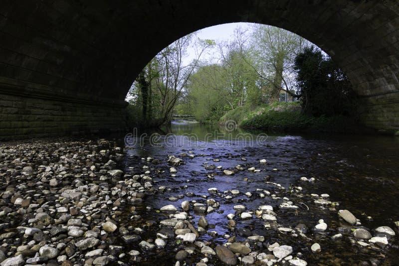 Pont en pierre avec la rivière peu profonde fonctionnant dessous photographie stock libre de droits