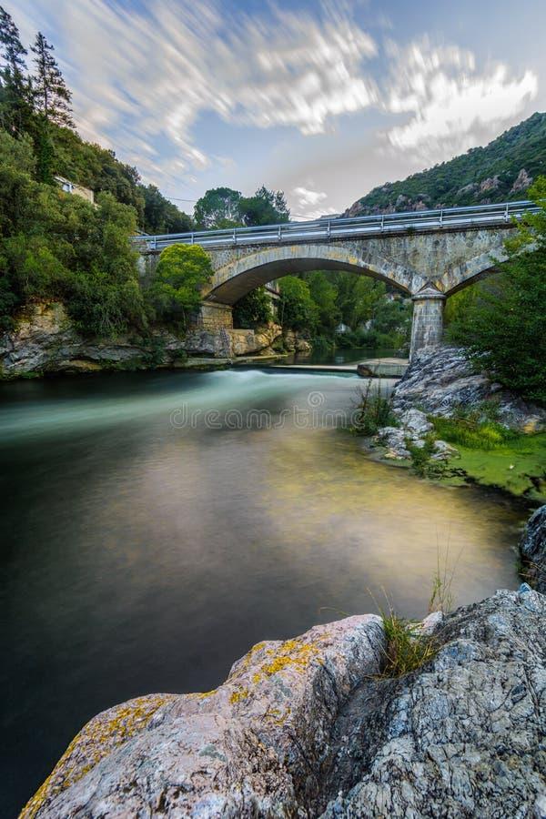 Pont en pierre, rivière colorée et nuages photo stock
