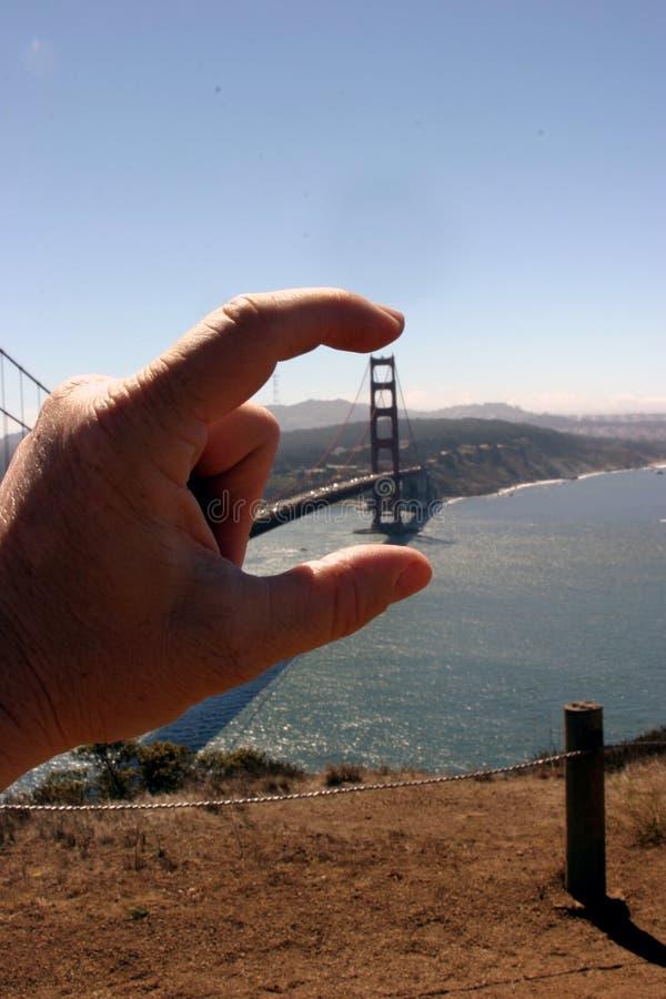 Pont en porte de Goldeng entre mes doigts photo libre de droits