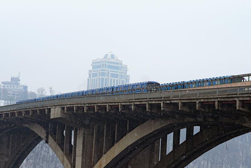 Pont en souterrain de métro avec deux trains Le train de métro monte le pont Neige légère, matin d'hiver image libre de droits