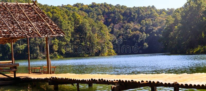 Pont et hutte en bambou dans le lac et le camping avec des pins photographie stock
