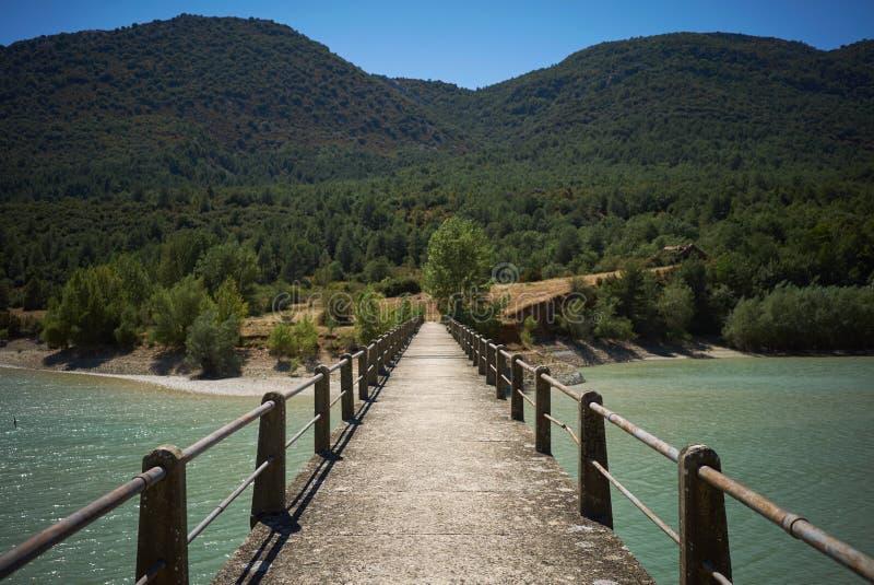 Pont piétonnier concret au-dessus d'une baie parmi les collines vertes image libre de droits