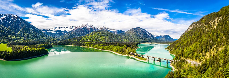 Pont stupéfiant au-dessus de lac Sylvenstein, Bavière supérieure d'accumulation Silhouette d'homme se recroquevillant d'affaires  photographie stock libre de droits