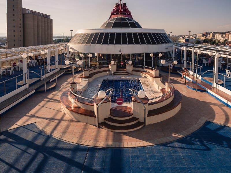 Pont supérieur d'un ferry avec la piscine au coucher du soleil image libre de droits