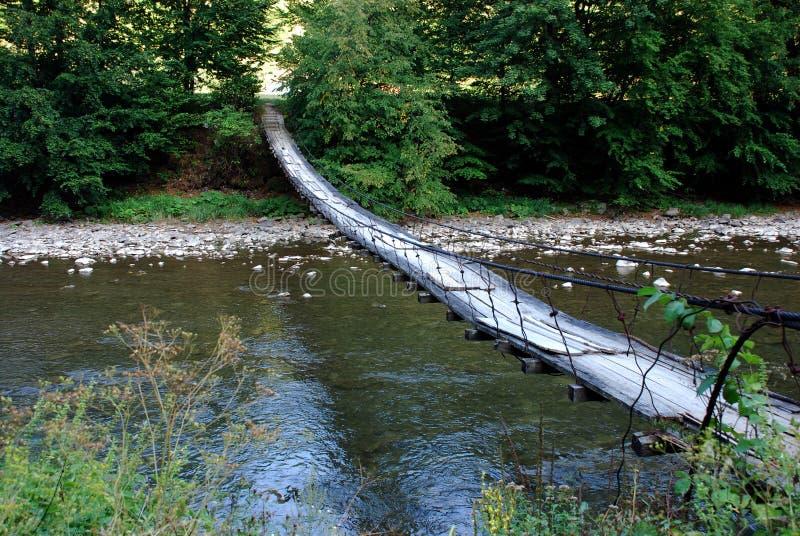 Pont suspendu au-dessus d'une rivière de montagne photographie stock