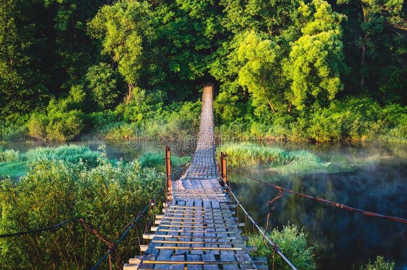 Pont suspendu au-dessus de la rivière sur laquelle les gens marchent photographie stock