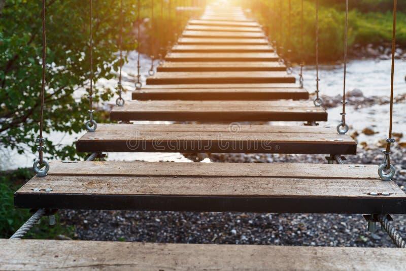 Pont suspendu en bois au-dessus d'une rivière de montagne menant dans les montagnes et la forêt images libres de droits