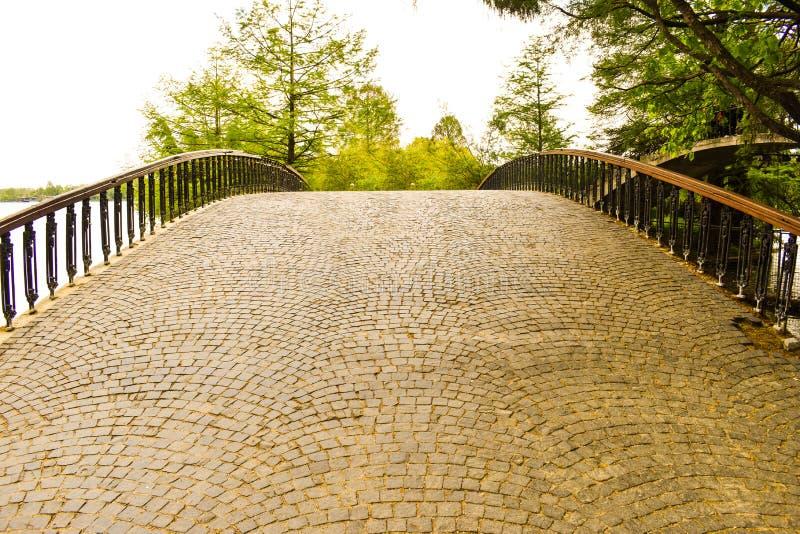 Pont vide d'arc de cru en parc de Herastrau de Bucarest au beau jour de ressort images stock