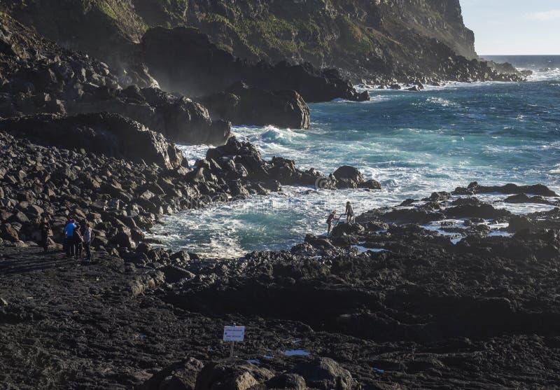 Ponta da Ferraria, sao Miguel Island, isole delle Azzorre, Portogallo 26 dicembre 2018: giovane womaman che prova al climbe giù a fotografie stock