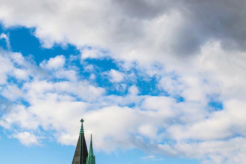 Ponta de uma torre da igreja contra nuvens bonitas e um c?u azul foto de stock royalty free