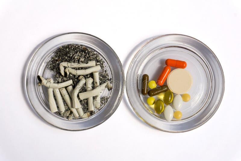 Pontas de cigarro e comprimidos imagem de stock