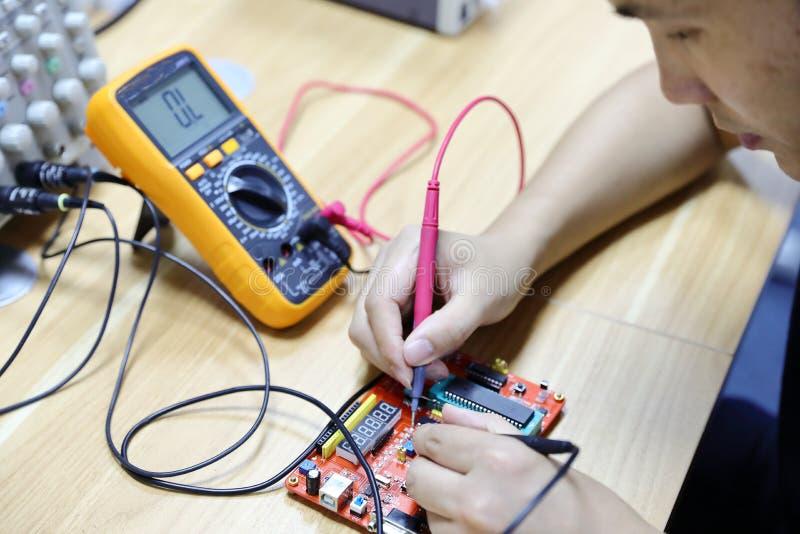 Pontas de prova do multímetro que examinam uma placa de circuito do computador imagem de stock royalty free