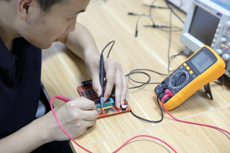 Pontas de prova do multímetro que examinam uma placa de circuito do computador imagem de stock