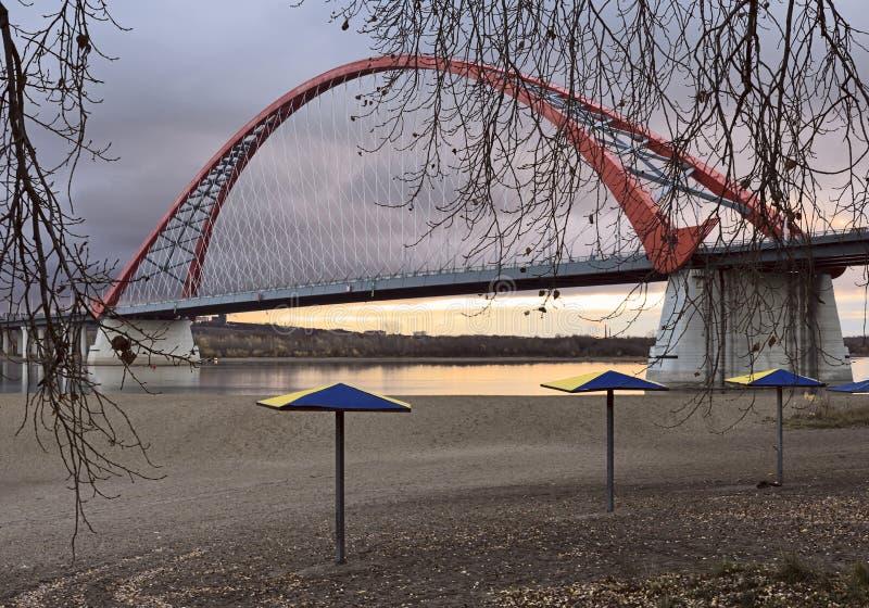 Ponte arqueada sobre o Rio Ob com guarda-chuvas de praia fotografia de stock